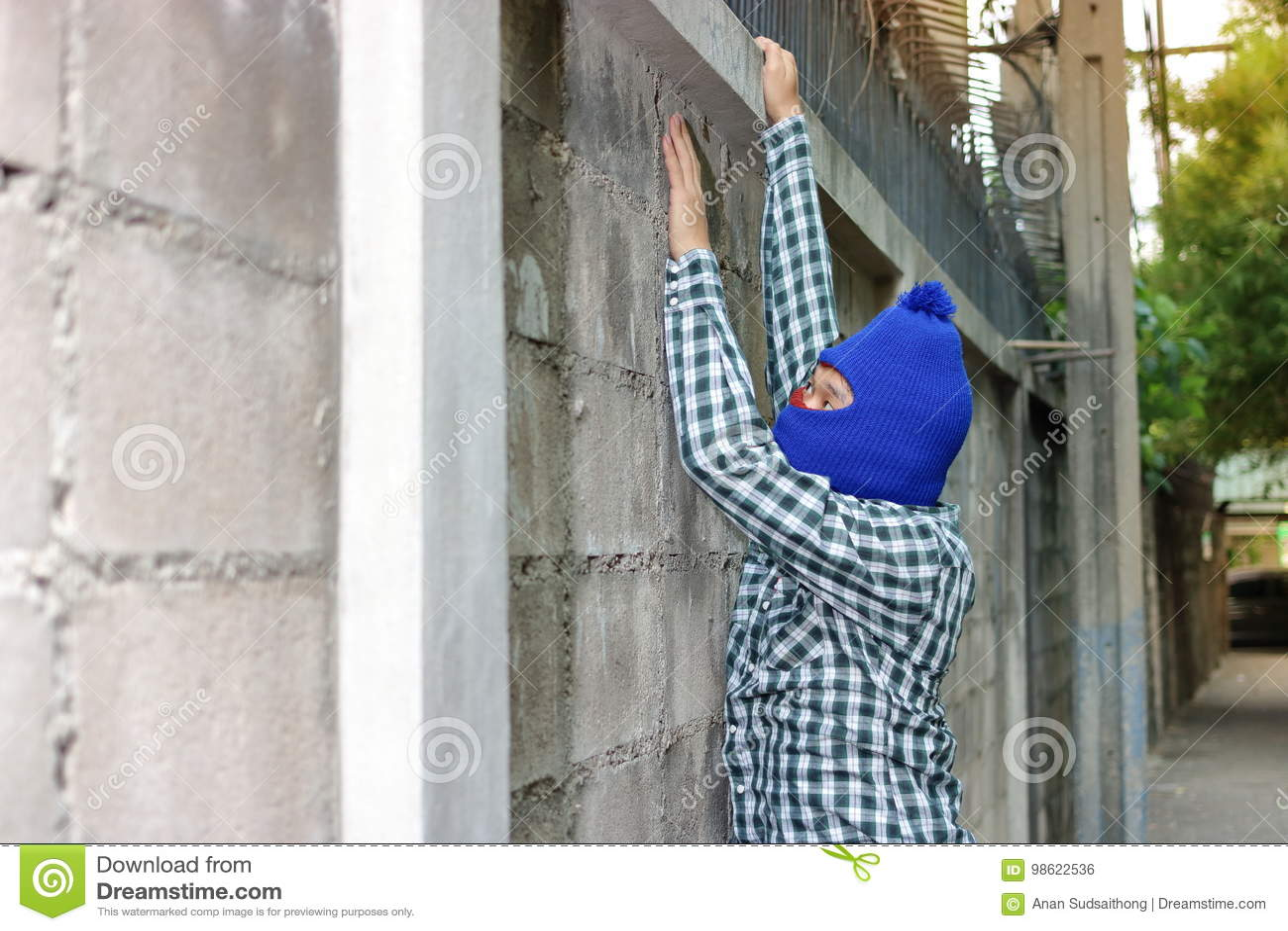 Ladrão em uma máscara que escala através de uma cerca