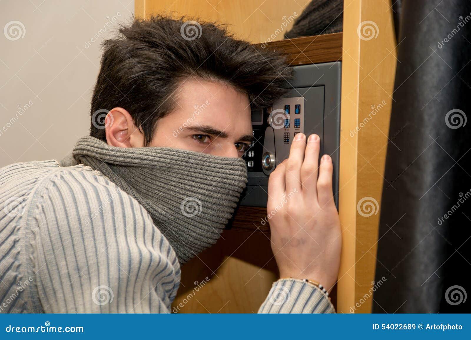 Ladrón masculino joven que abre una pequeña cámara acorazada casera o