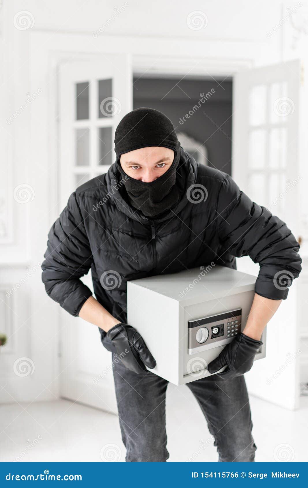 Ladrón que mira la cámara con el pasamontañas negro que roba la caja segura electrónica moderna El ladrón confía un crimen adentr