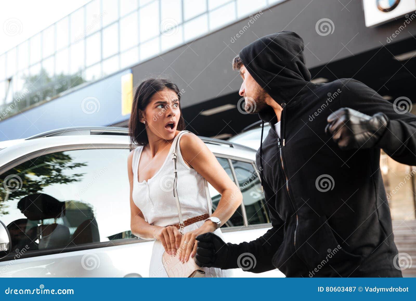 Ladro aggressivo del giovane in maglia con cappuccio che ruba donna spaventata