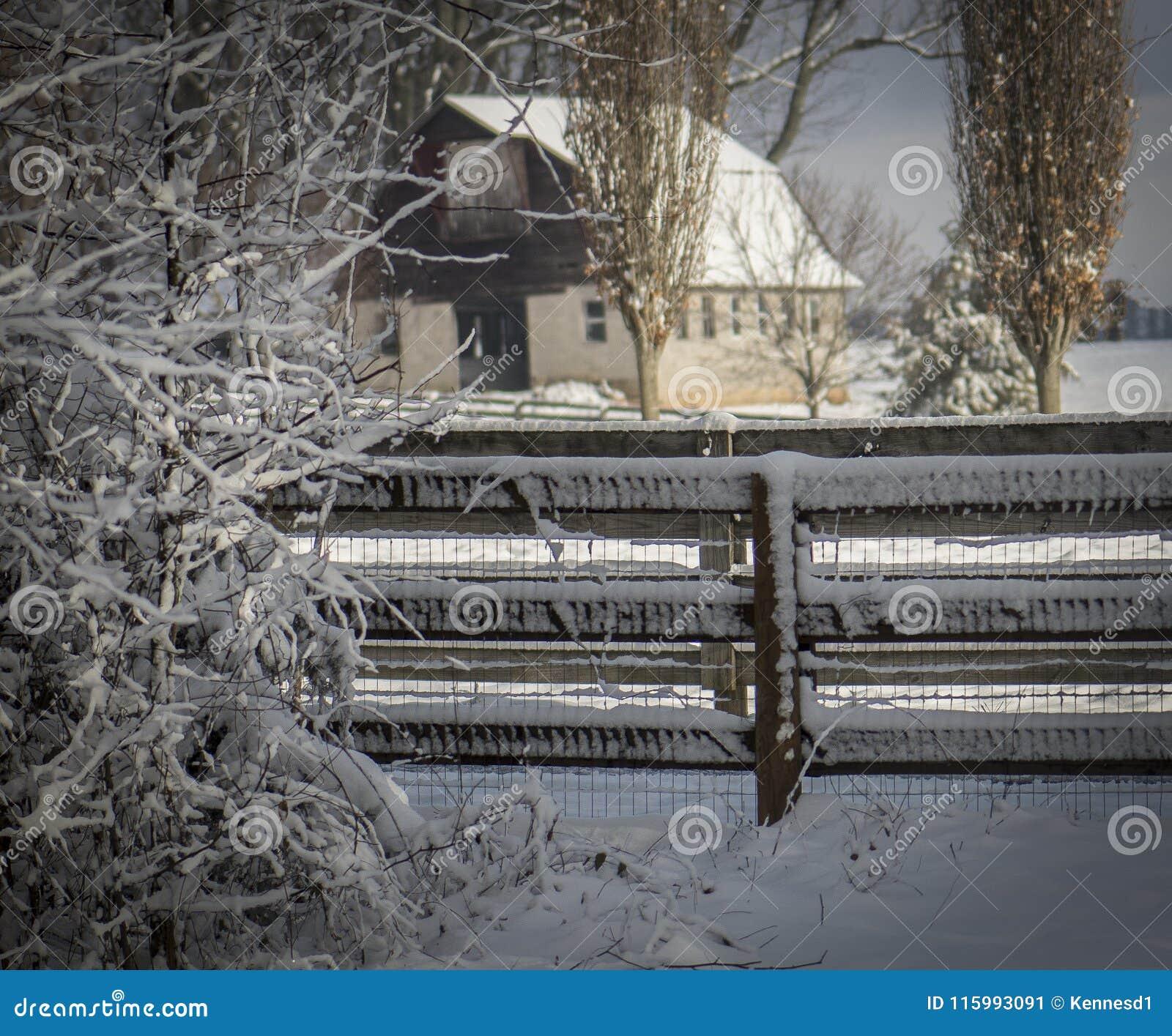Ladugård och staket i snöig fält