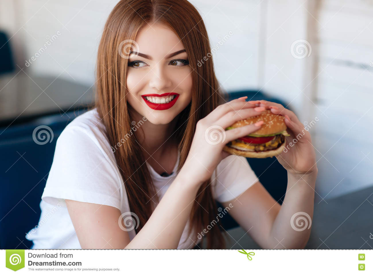 Red Lipstick Brown Hair Blue Eyes: Lady With A Hamburger For A Table In A Cafe Stock Photo
