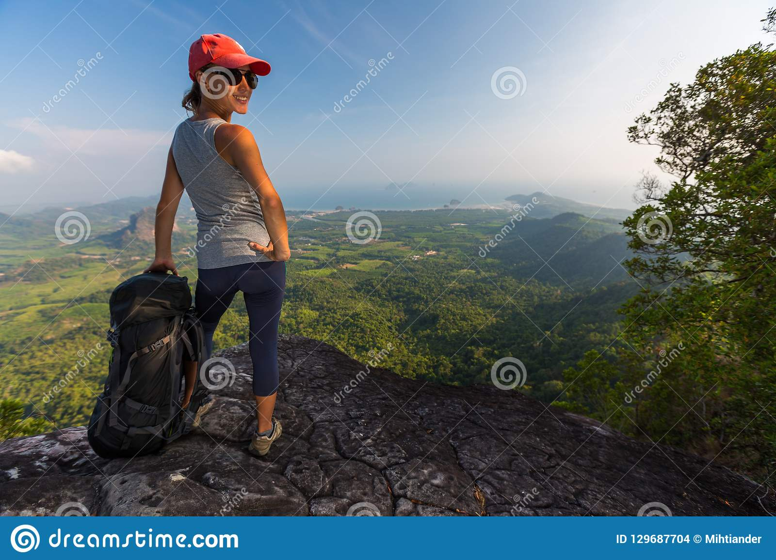 Lady hiker stands on the cliff