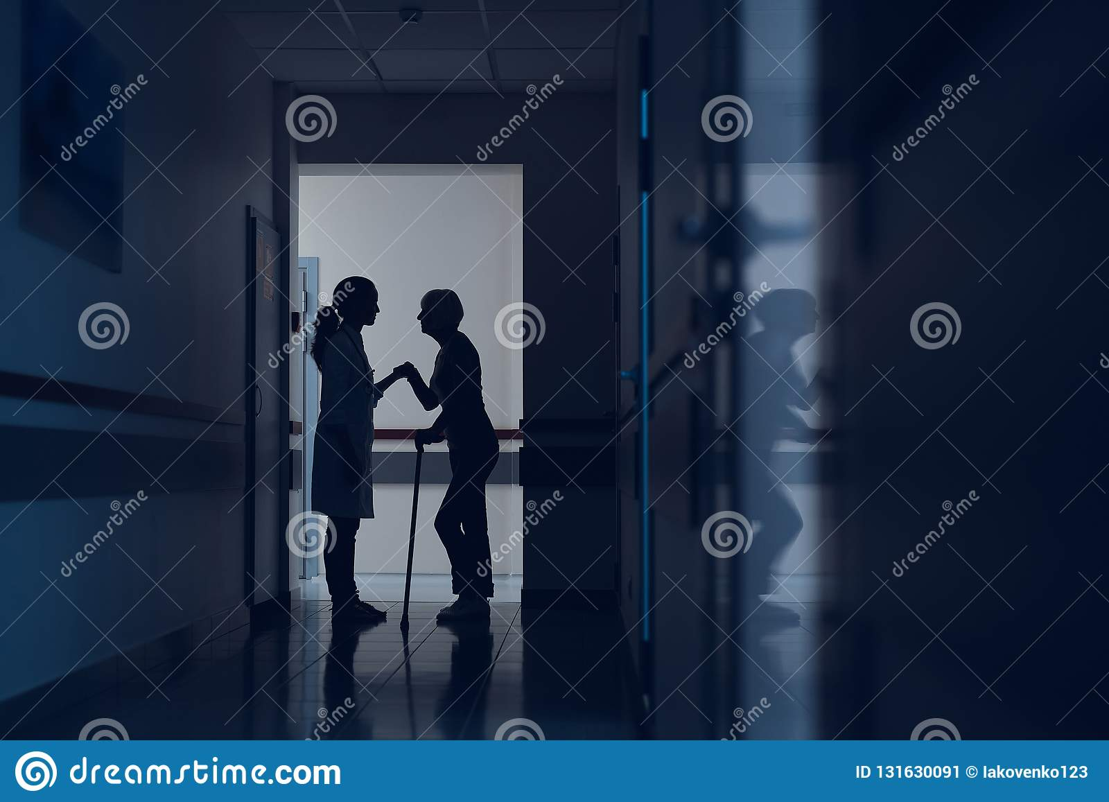 Lady is leaning on doctor and cane in hallway