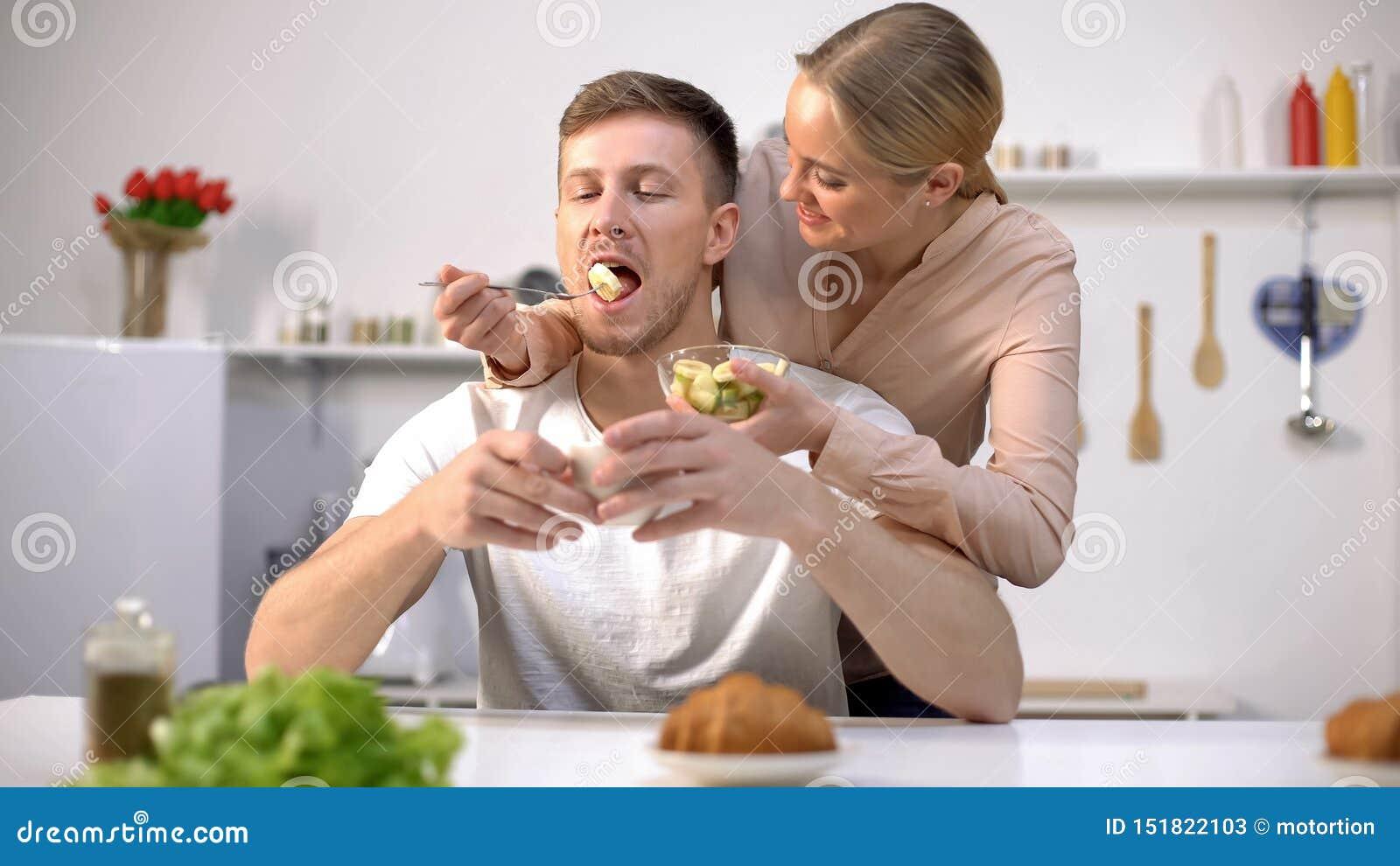 Lady playfully feeding husband with slice of banana, fruits as tasty vitamins