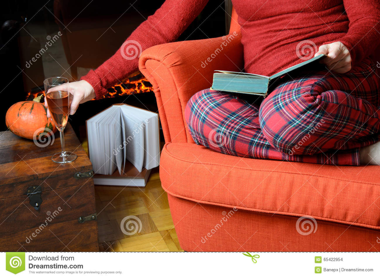 lady reading and relaxing by the fireplace stock photo image