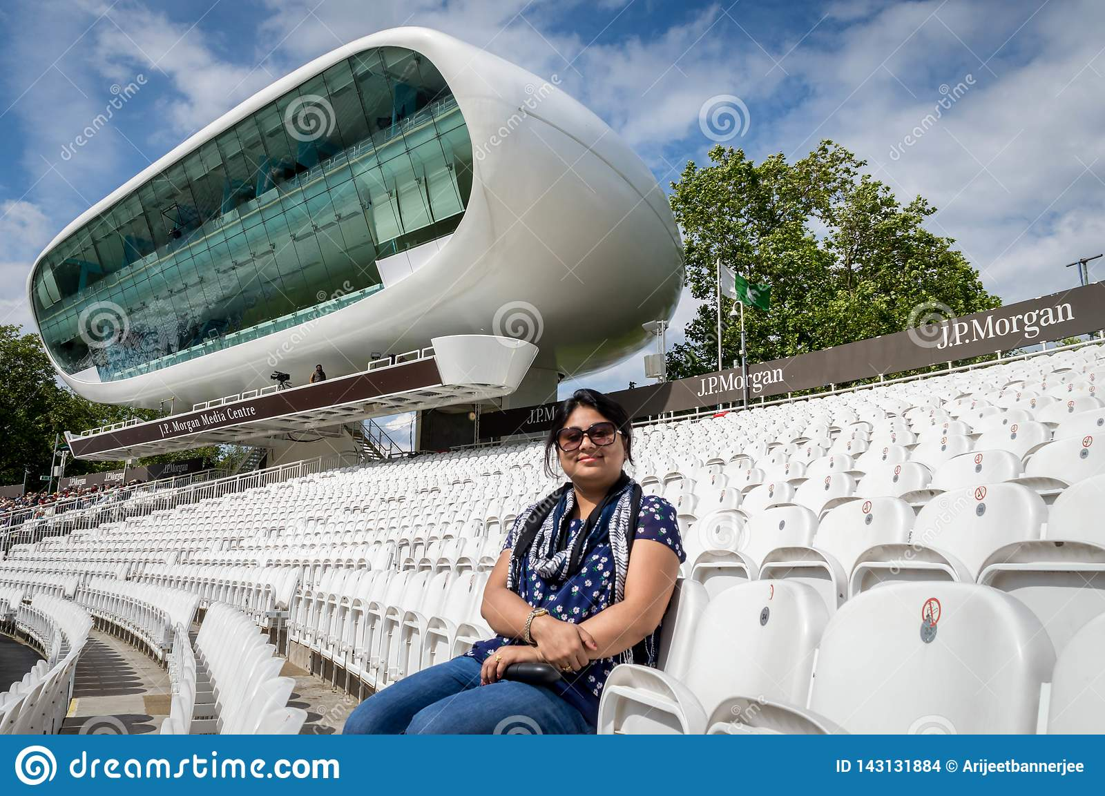 A lady sitting on the empty pavilion of Lord`s Cricket Ground with the media center in