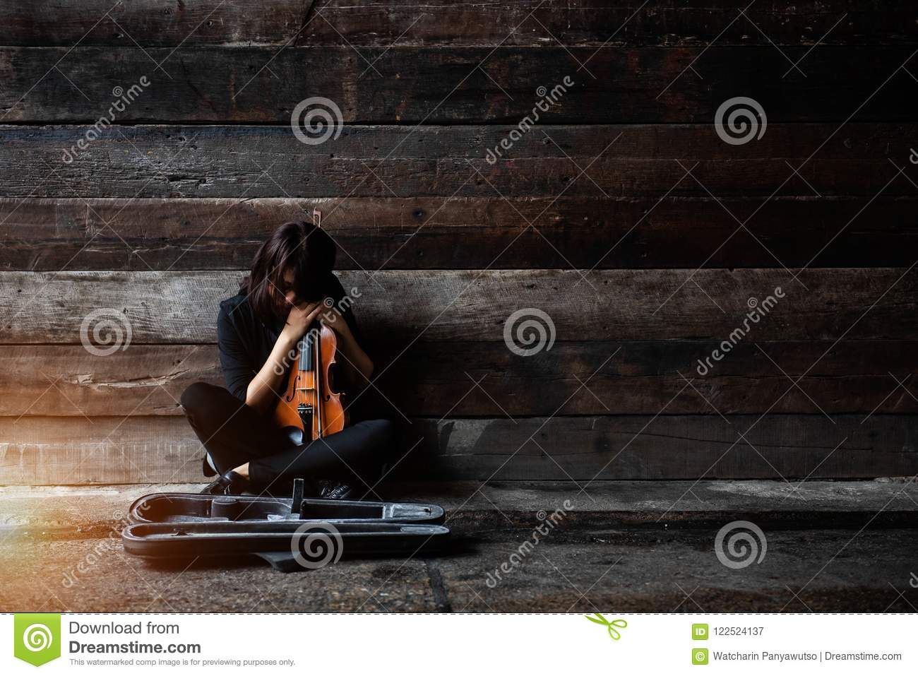 The lady is sitting on grunge surface cement floor,hold violin and bow in her arms,turn face down to volin,vintage and art style