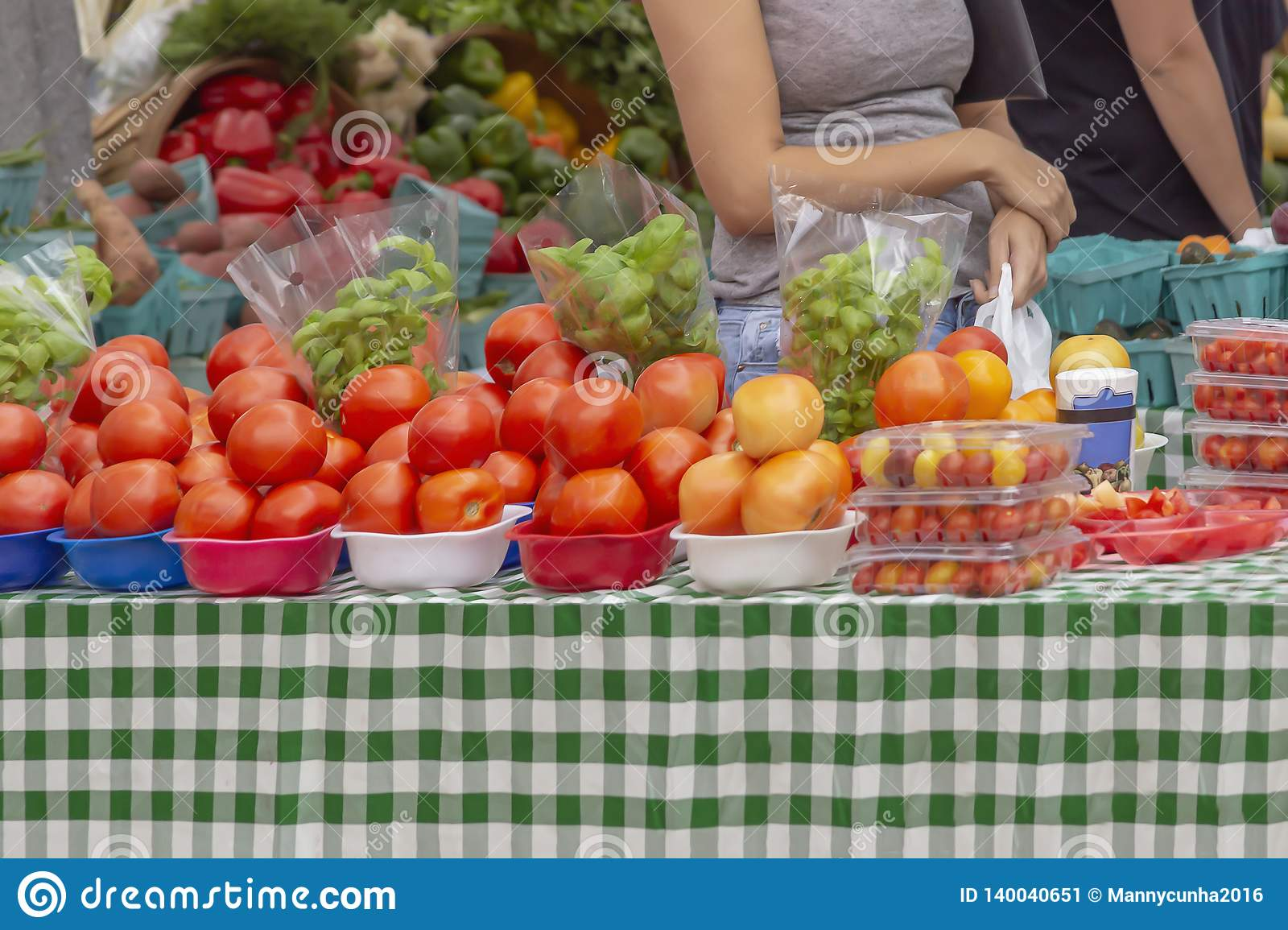A lady stops at a table filled with vibrant red tomatoes at the outdoor market