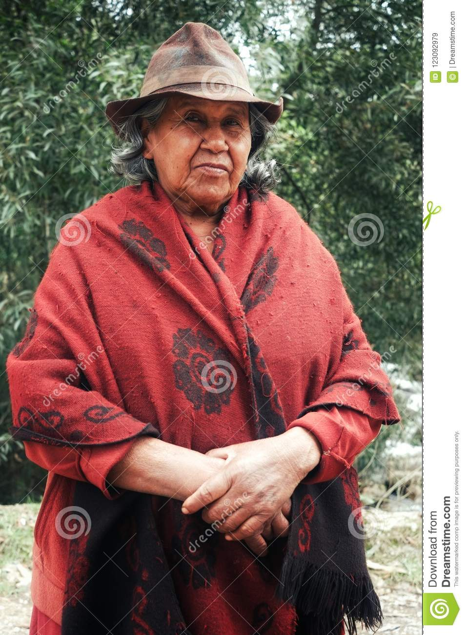 Lady in traditional hat and poncho in front of eucalyptus trees