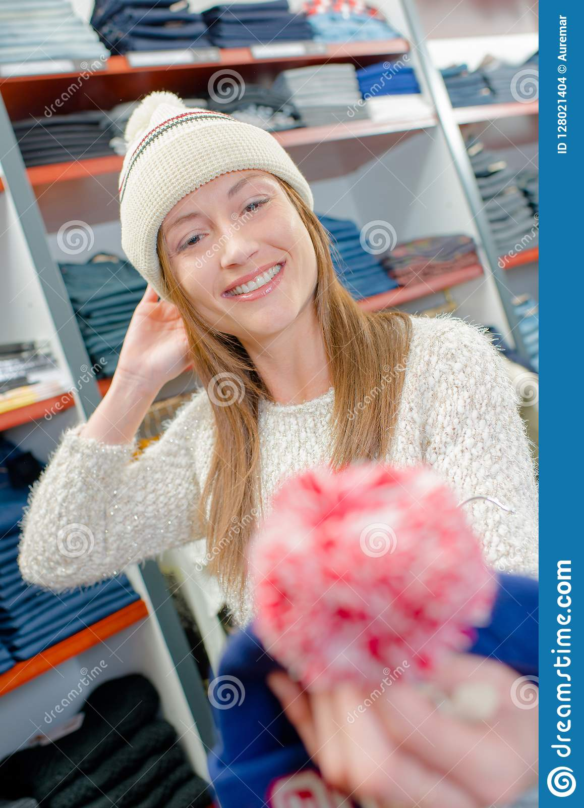 Lady wearing bobble hat in clothes shop