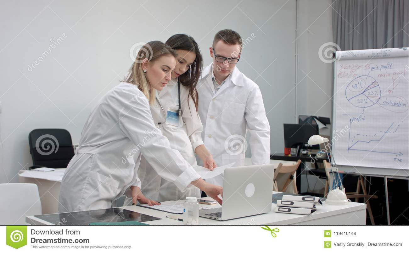 Lag av doktorer som arbetar på bärbara datorn och analyserar röntgenstrålen i medicinskt kontor
