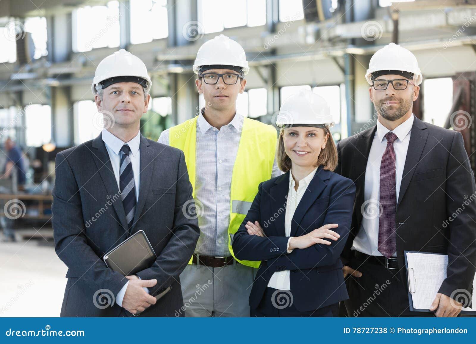 Lag av säkra bärande hardhats för affärsfolk i metallbransch