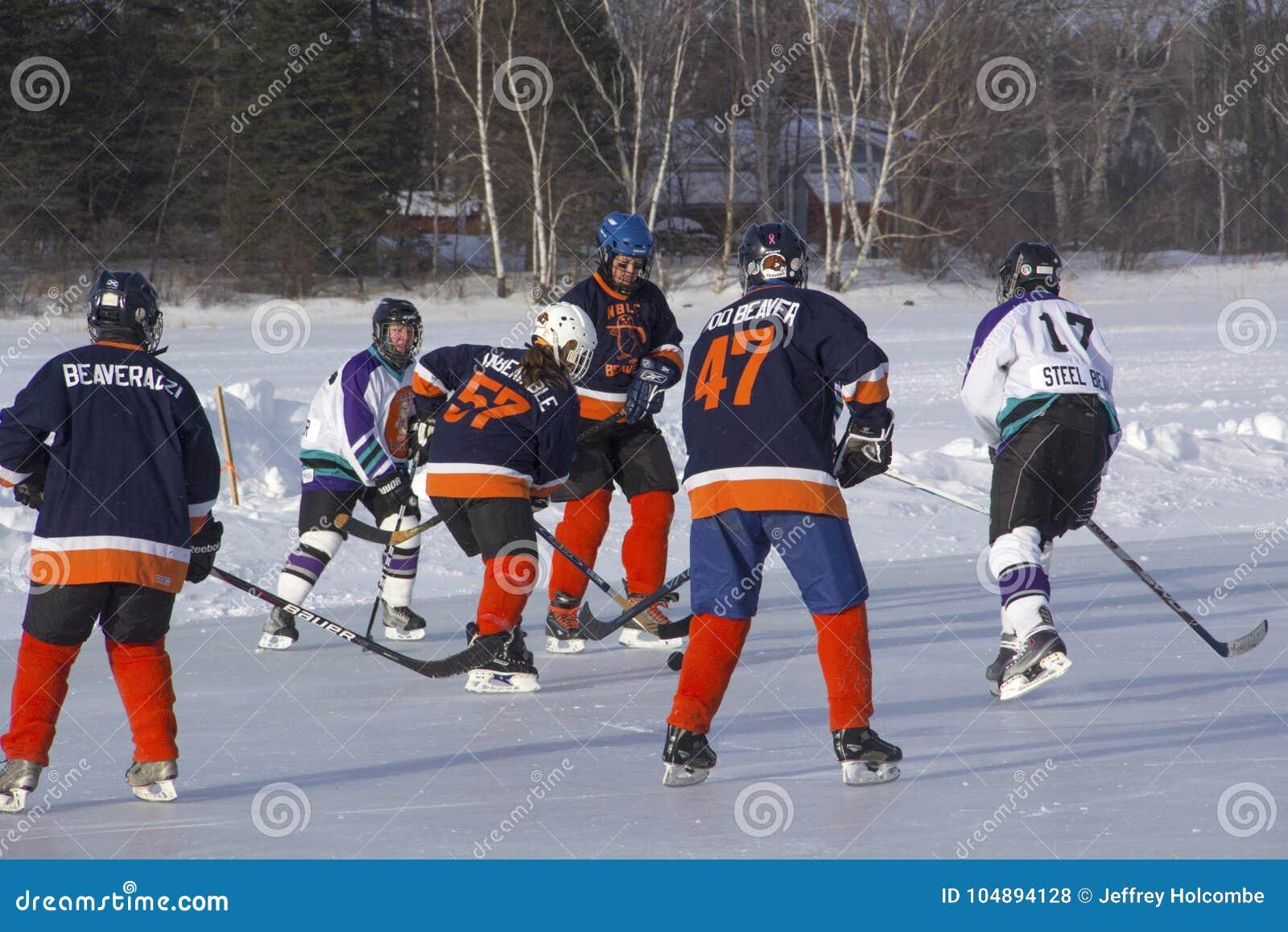 Lag för kvinna` s konkurrerar i en dammhockeyfestival i Rangeley