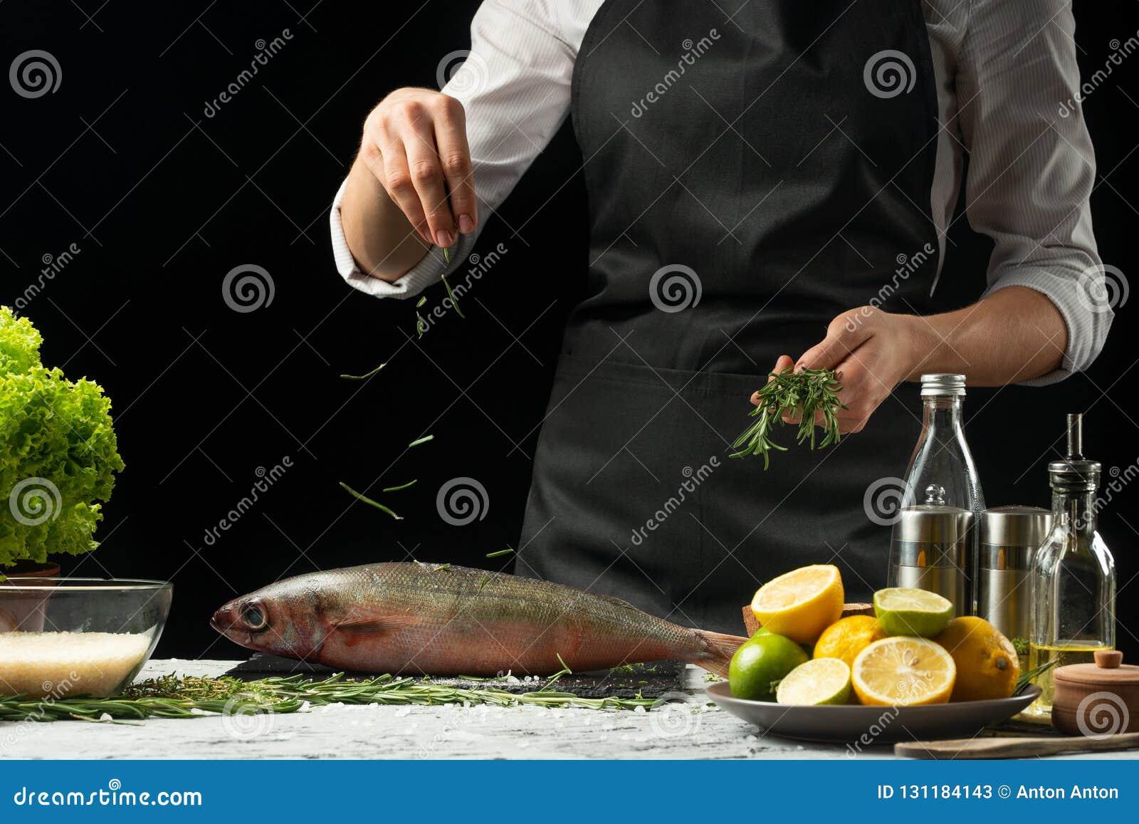 Laga mat chefen av ny fisk, strilar kocken den krydda fisken på en svart bakgrund med citroner, limefrukter, rosmarin och thym