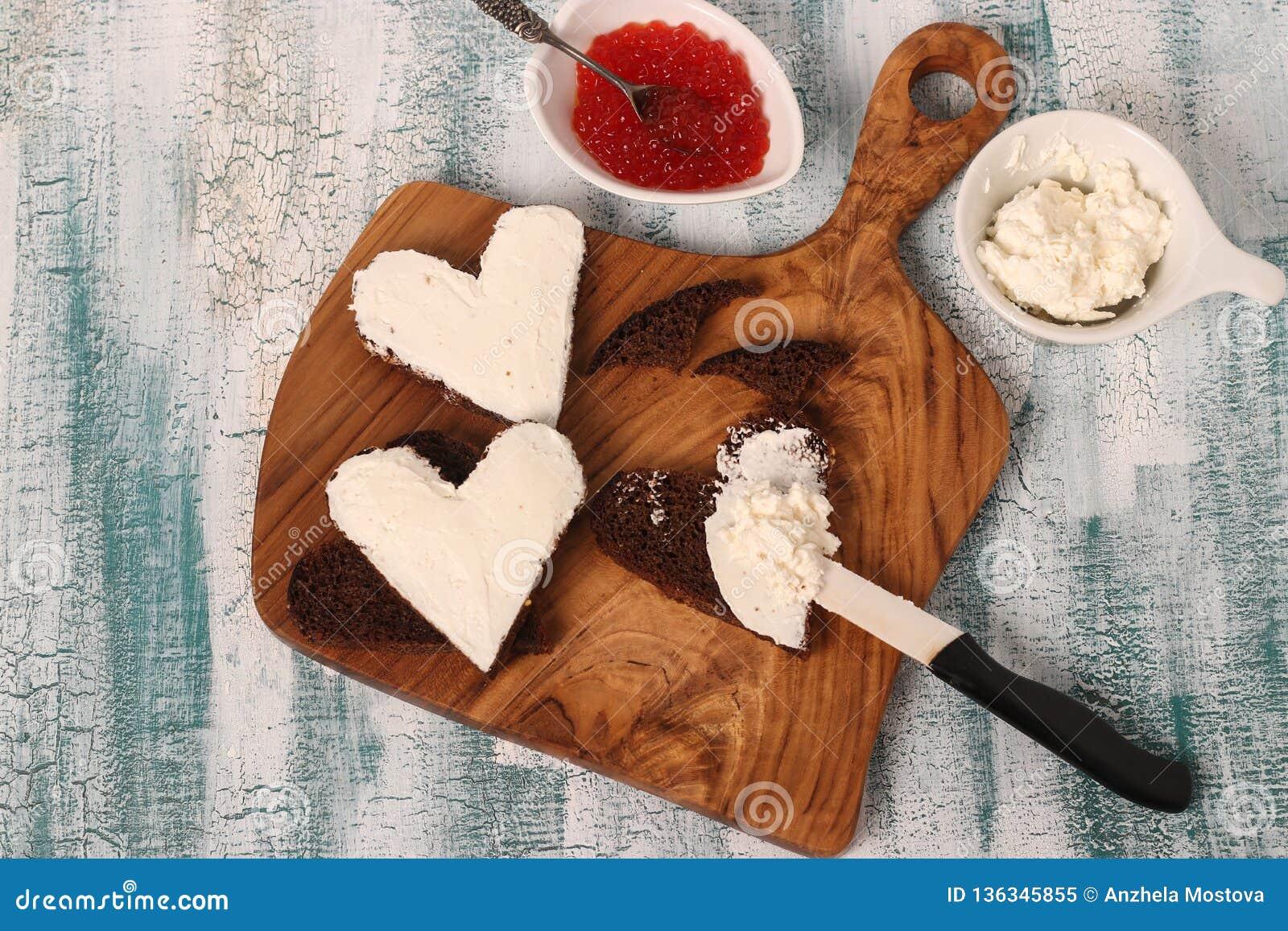 Laga mat smörgåsar med den röda kaviaren och gräddost i formen av en hjärta för valentin dag