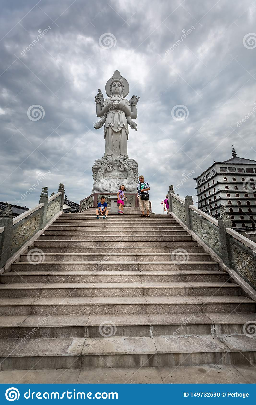 Lage hoekmening van een familie in Dragon Gate op steenstappen naast een groot Chinees standbeeld met dramatische hemel