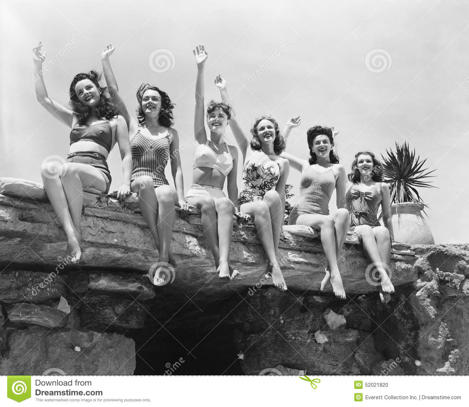 Lage hoekmening van een groep vrouwen die op een steenstructuur zitten en hun handen golven (Alle afgeschilderde personen zijn ge