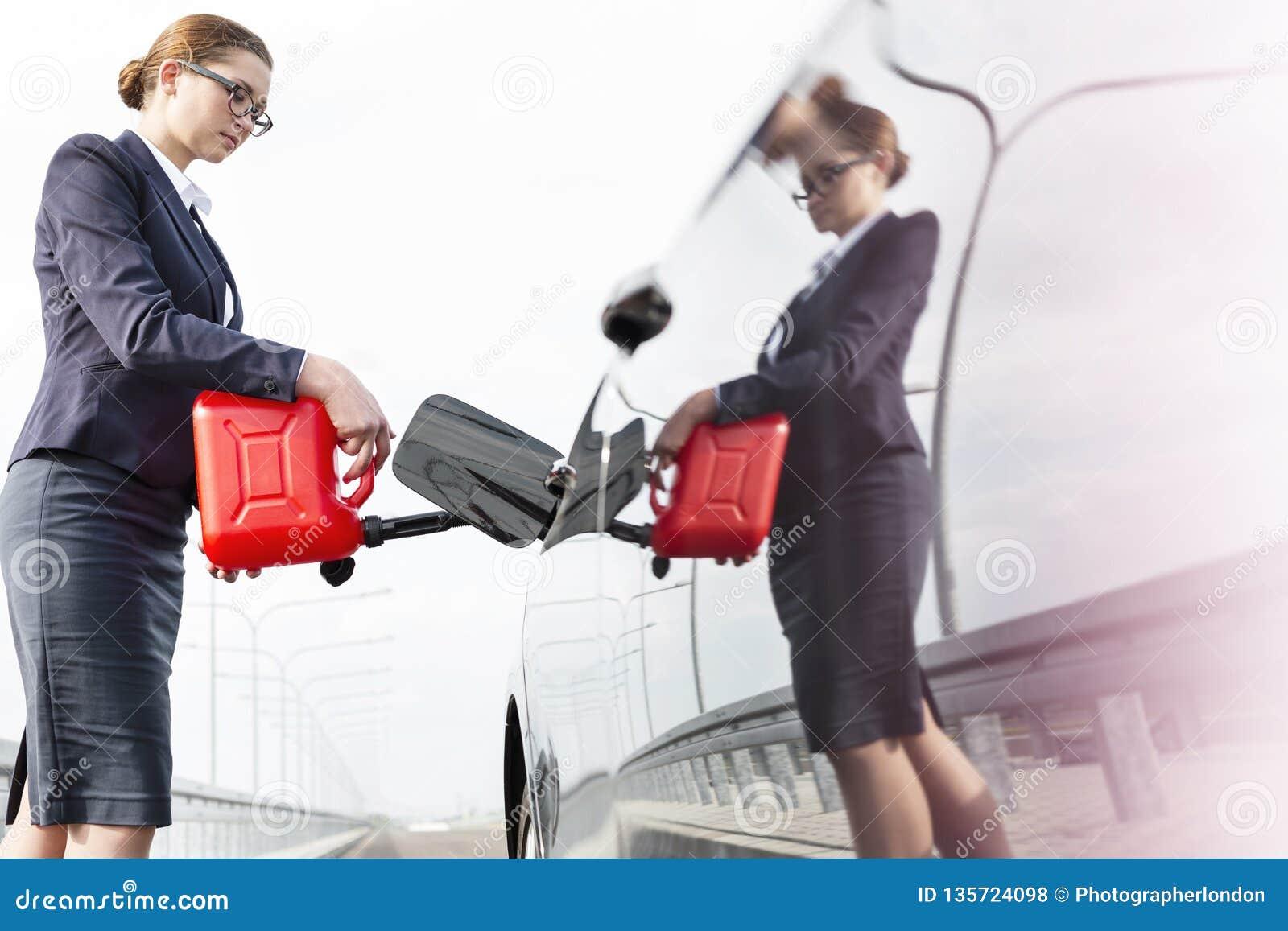 Lage hoekmening van stafmedewerker met bus die auto van brandstof voorzien tegen hemel