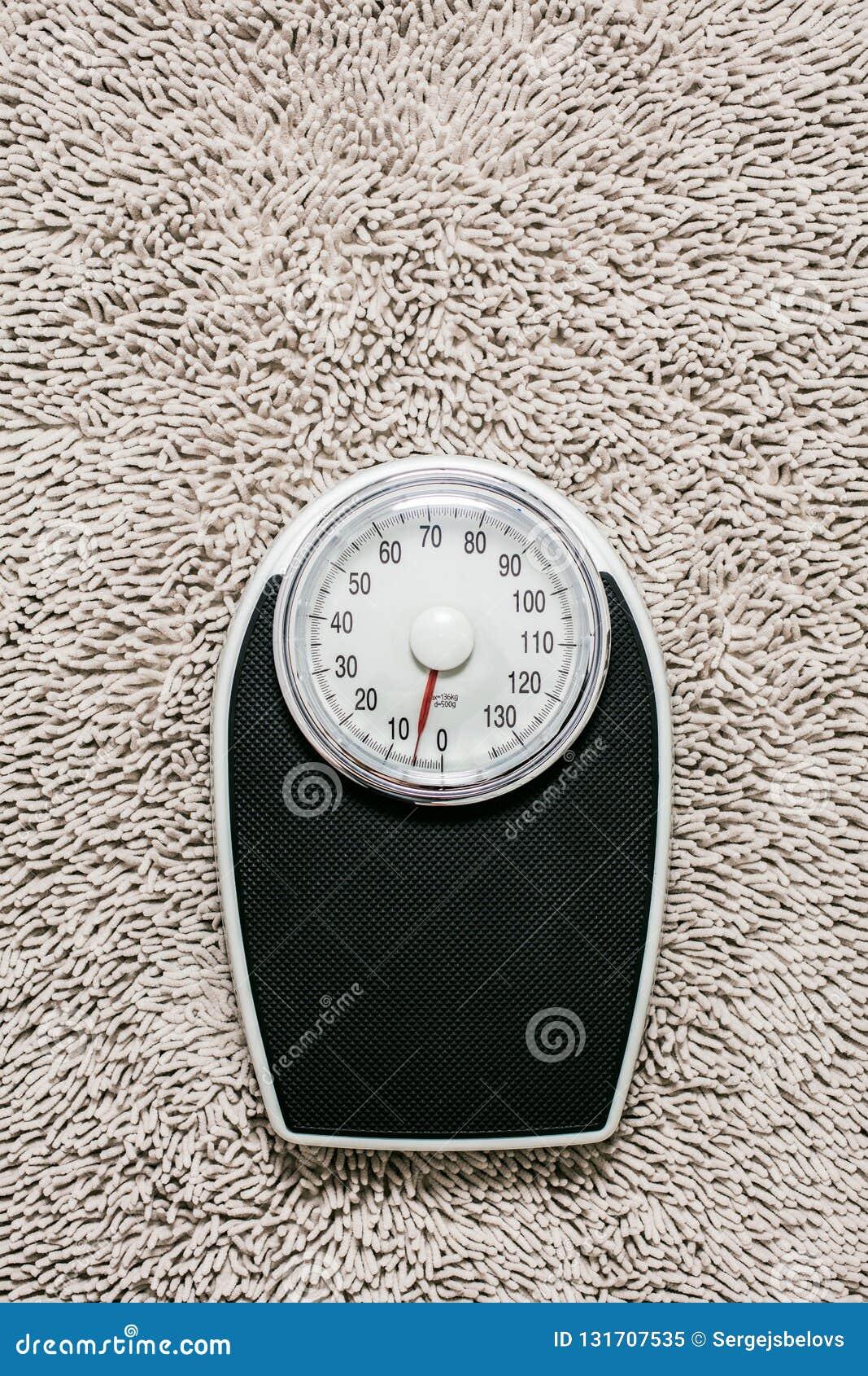 Lage sectie die van de mens zich op gewichtsschaal bevinden