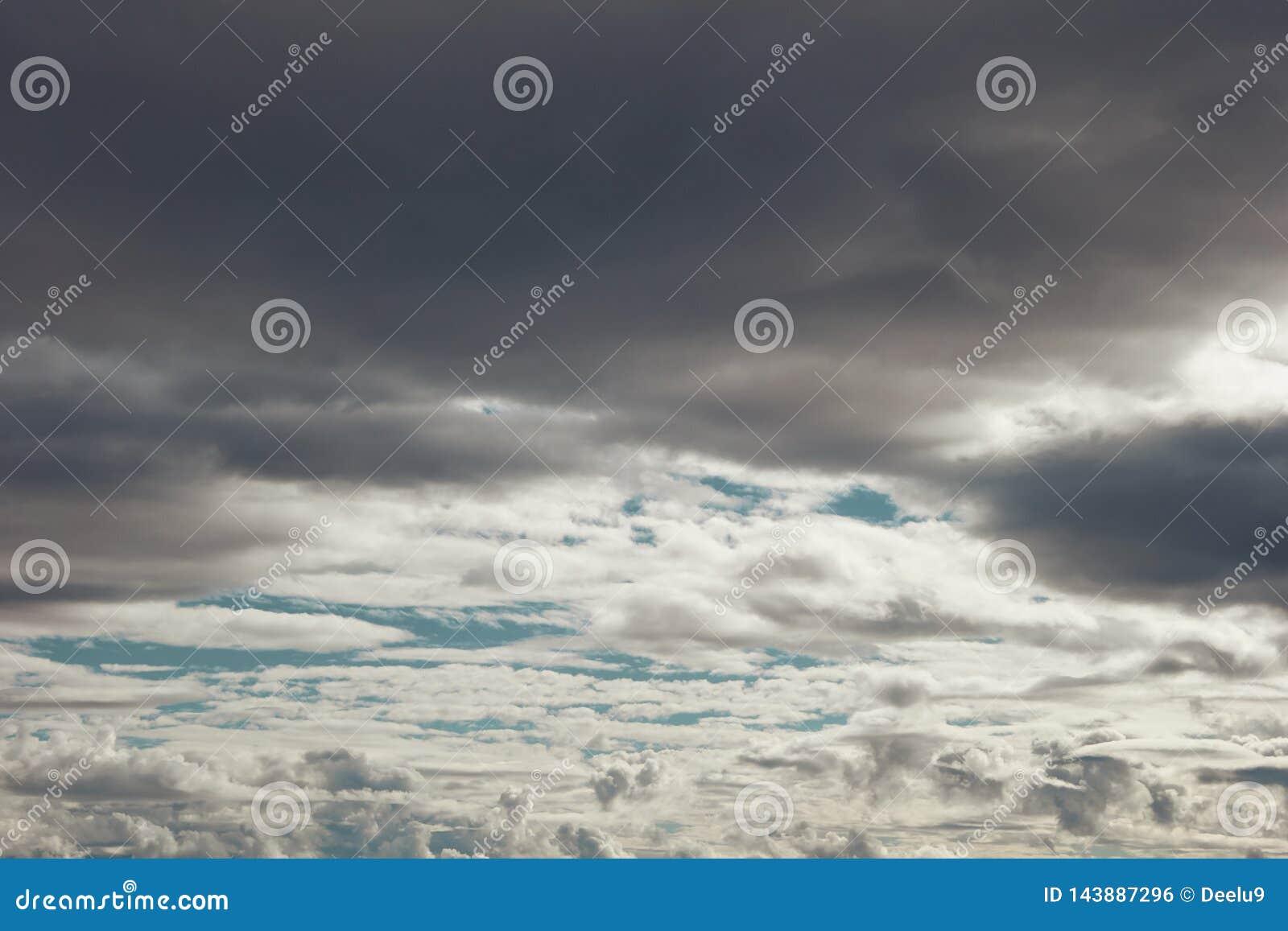 Lagen grijze en witte cloudes over blauwe hemel