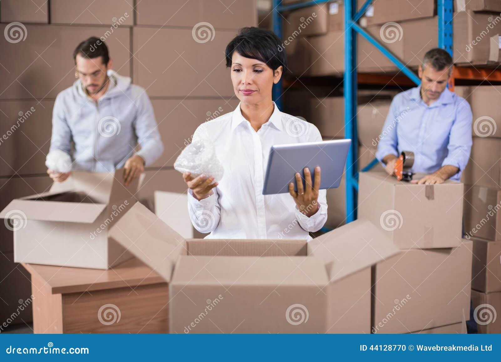 Lagerarbeitskräfte, die herauf Kästen verpacken
