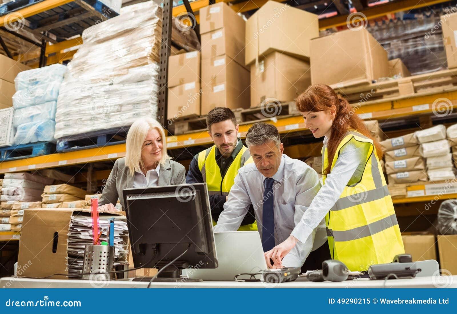 Lagermanager und -arbeitskraft, die an Laptop arbeiten
