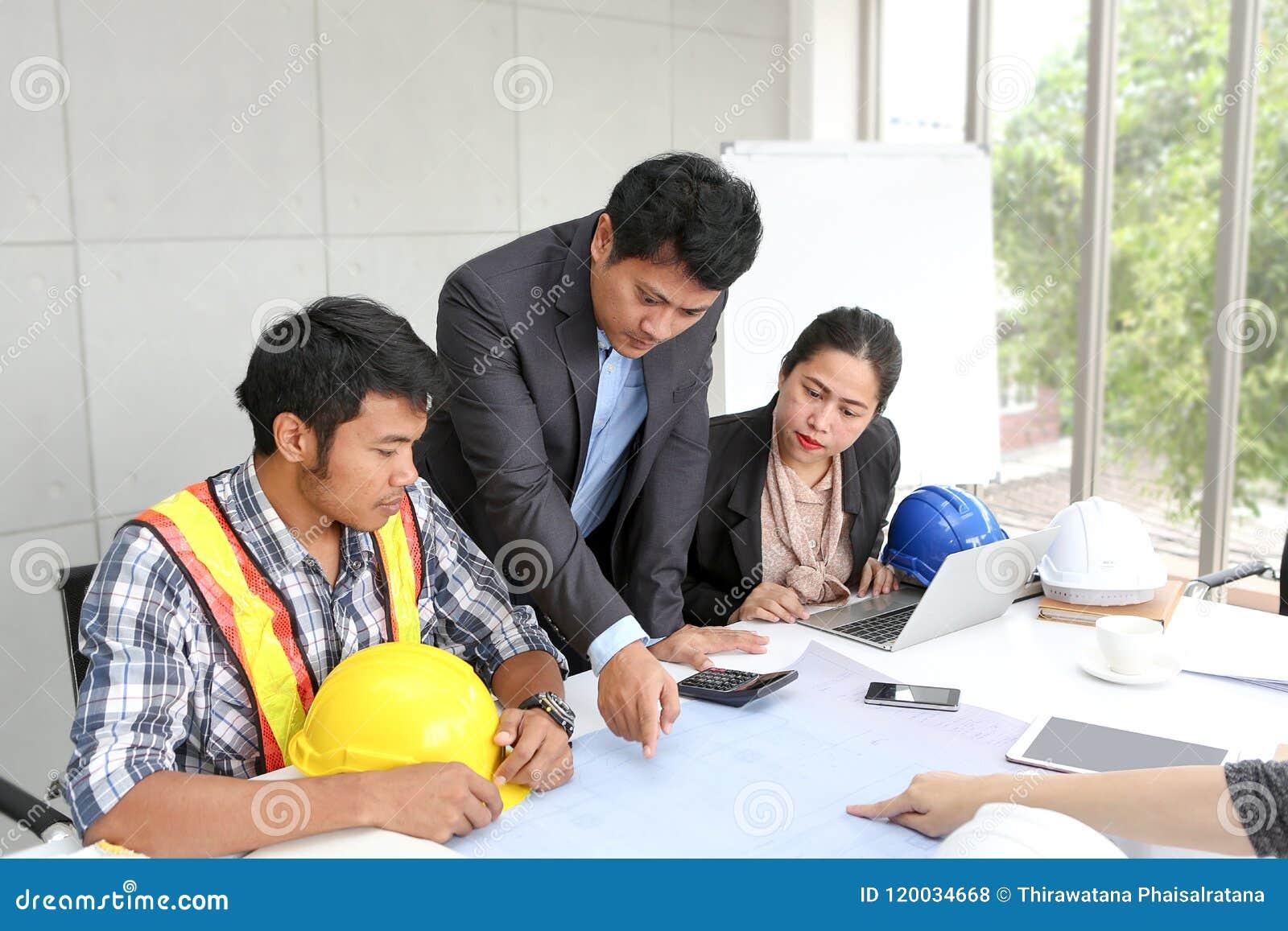 Laget iscensätter funktionsduglig mötesrum på kontoret Lagarbetare talar konstruktionsplan Elektrikersnickare eller tekniskt