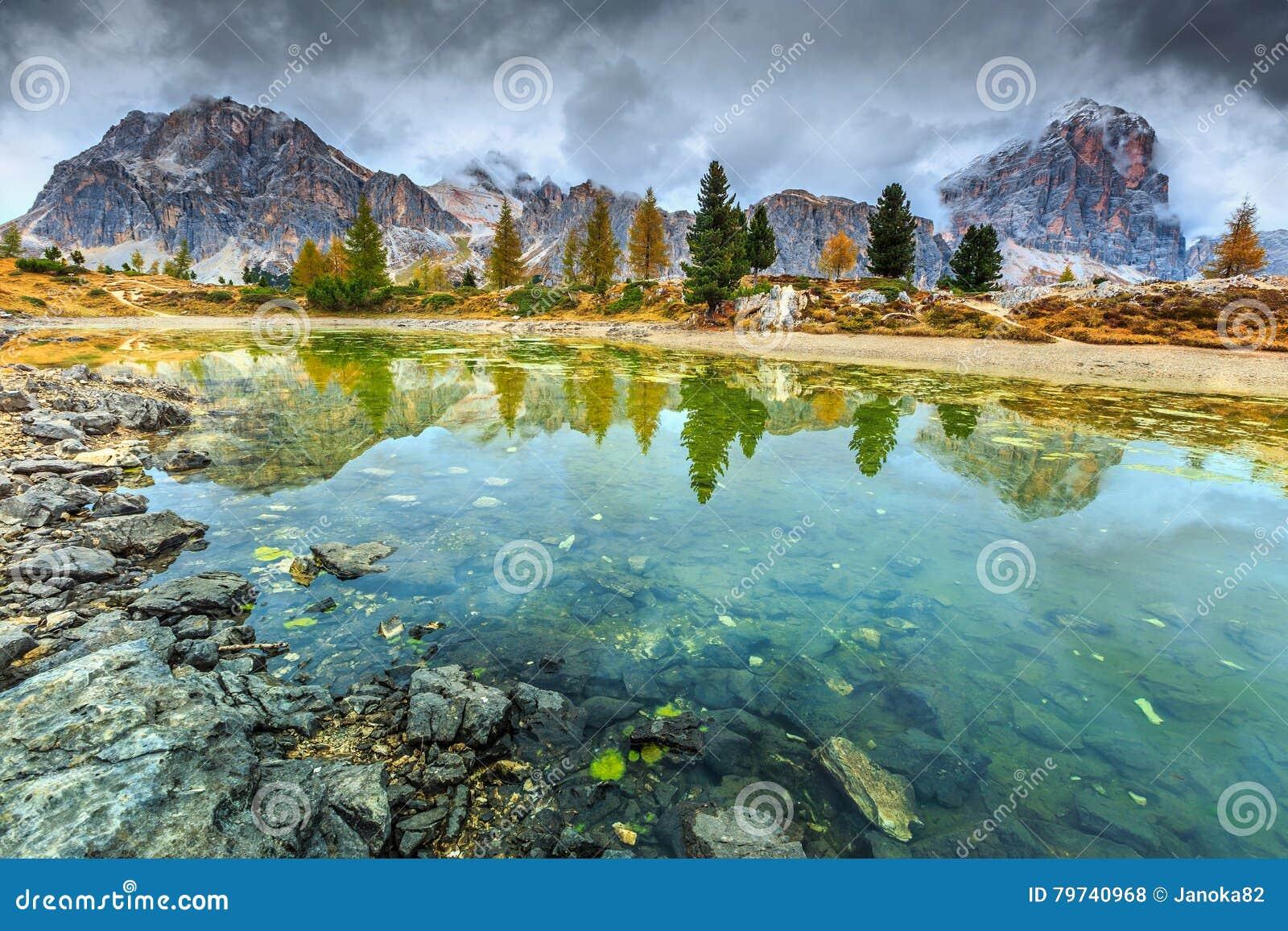 Lago alpino maravilloso con los picos brumosos en fondo, dolomías, Italia