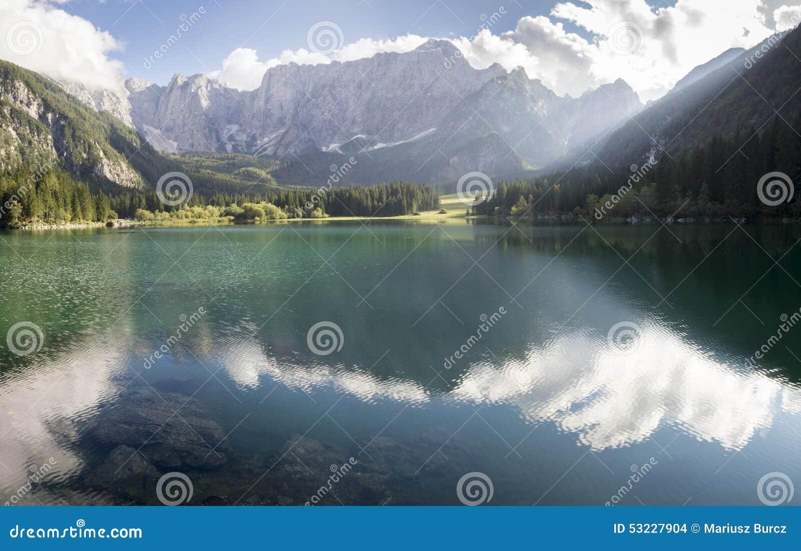 Lago alpino, salida del sol sobre el lago alpino Laghi di Fusine