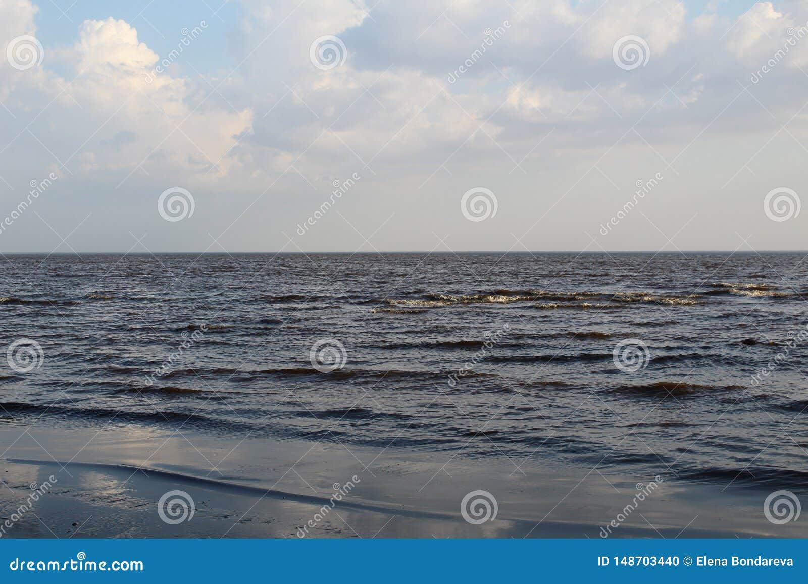Lago bianco con le onde e cielo blu in primavera