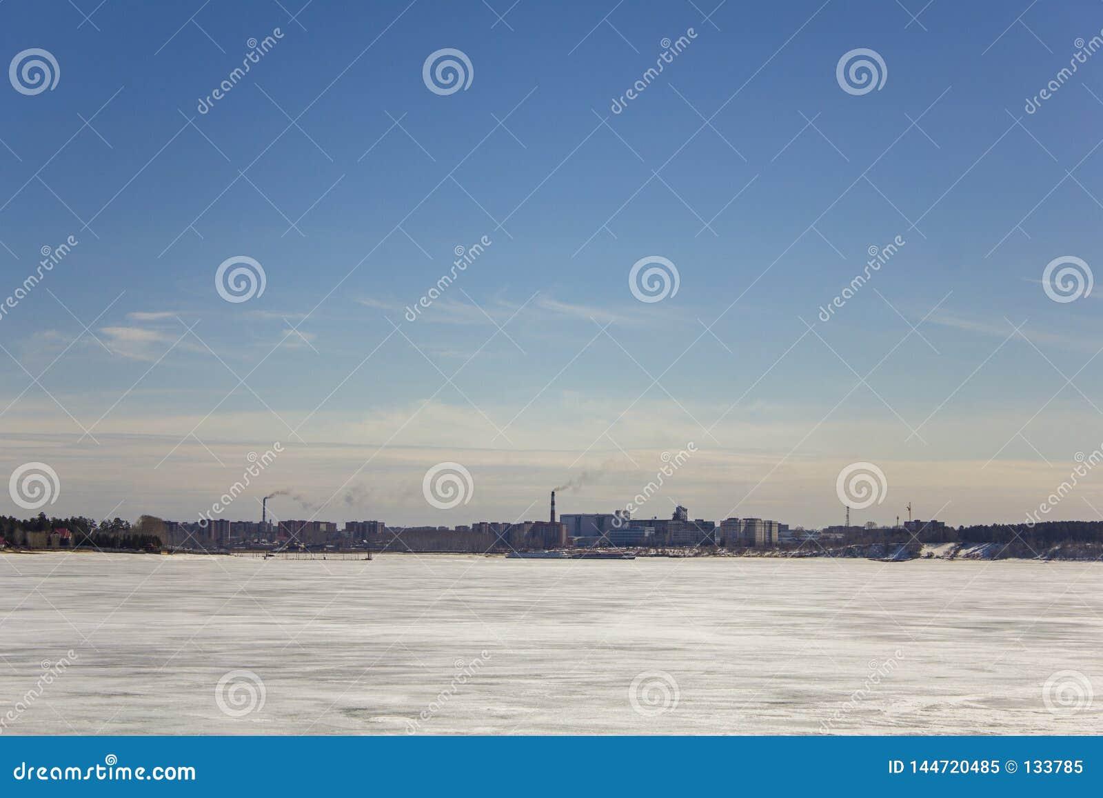 Lago bianco congelato della neve sui precedenti della città con i grattacieli ed i tubi enormi di fumo sotto un chiaro cielo blu