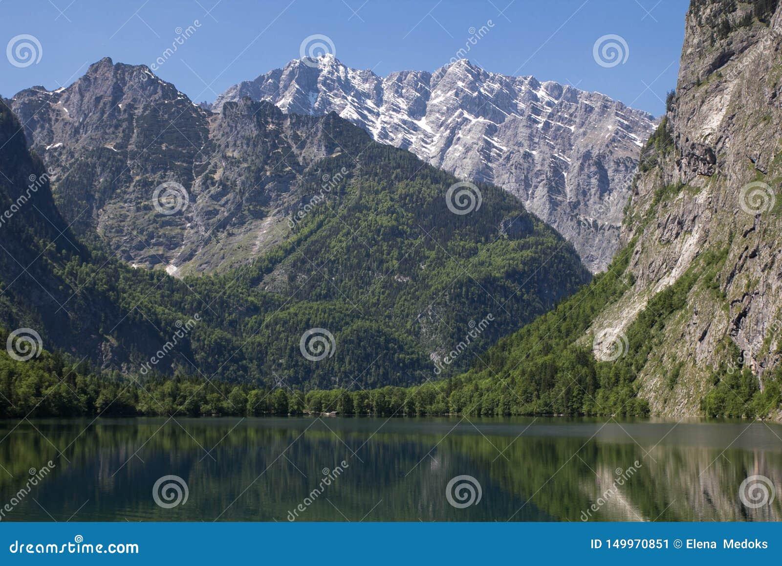 Lago com as montanhas claros da água na primavera Um lago pequeno na opinião dos cumes de uma costa Reflexão das montanhas dentro