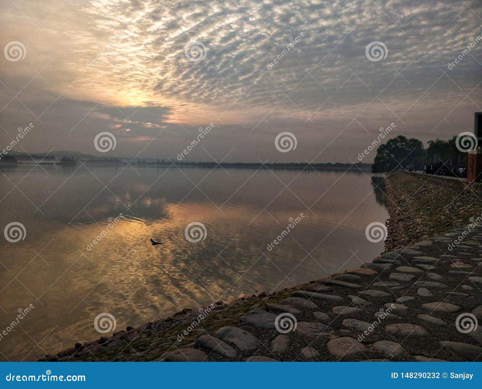 Lago con la salida del sol que hace manera a través de las nubes