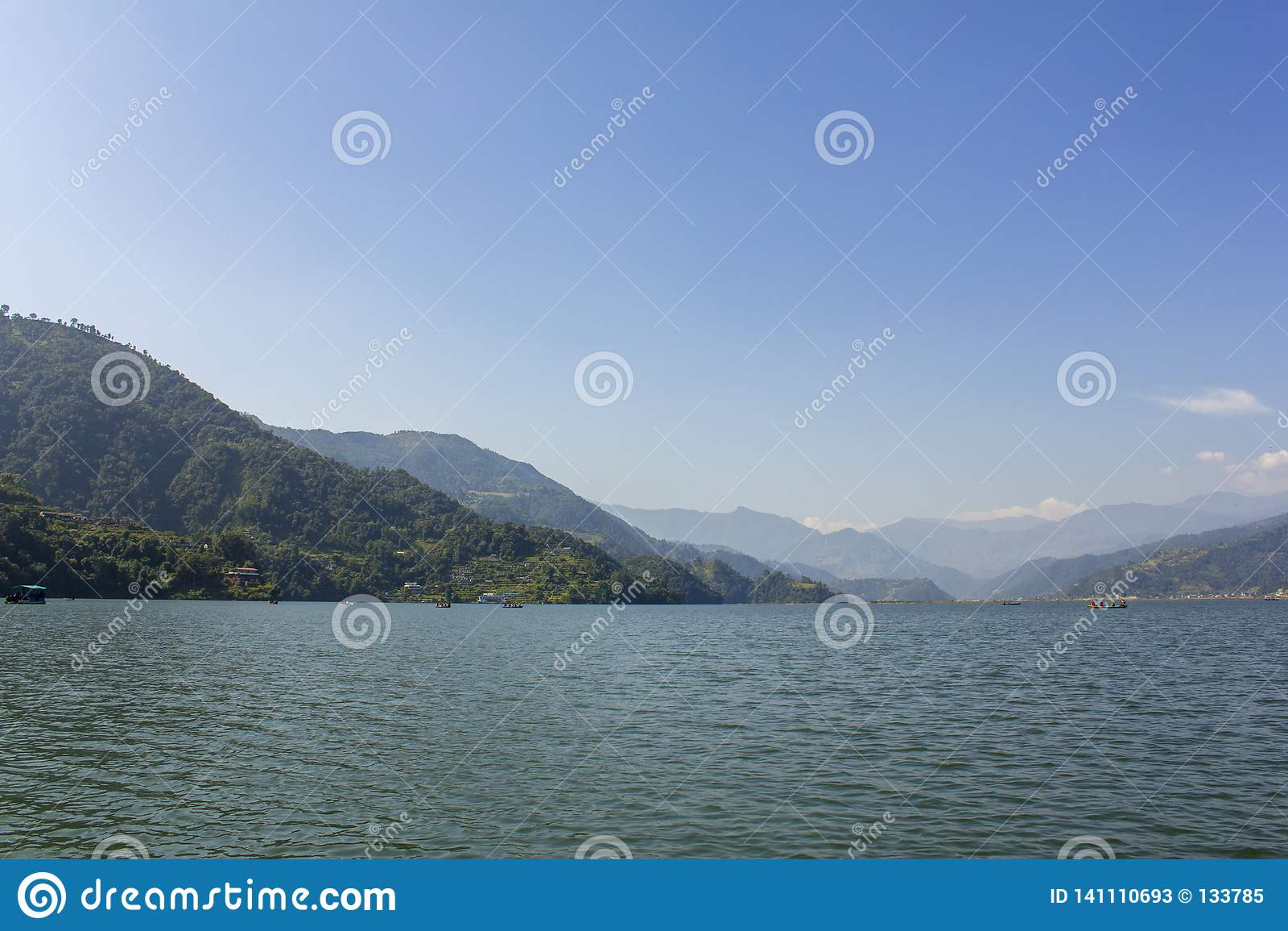 Lago con los barcos en el fondo de un valle verde de la montaña debajo del cielo azul, visión Phewa desde el agua