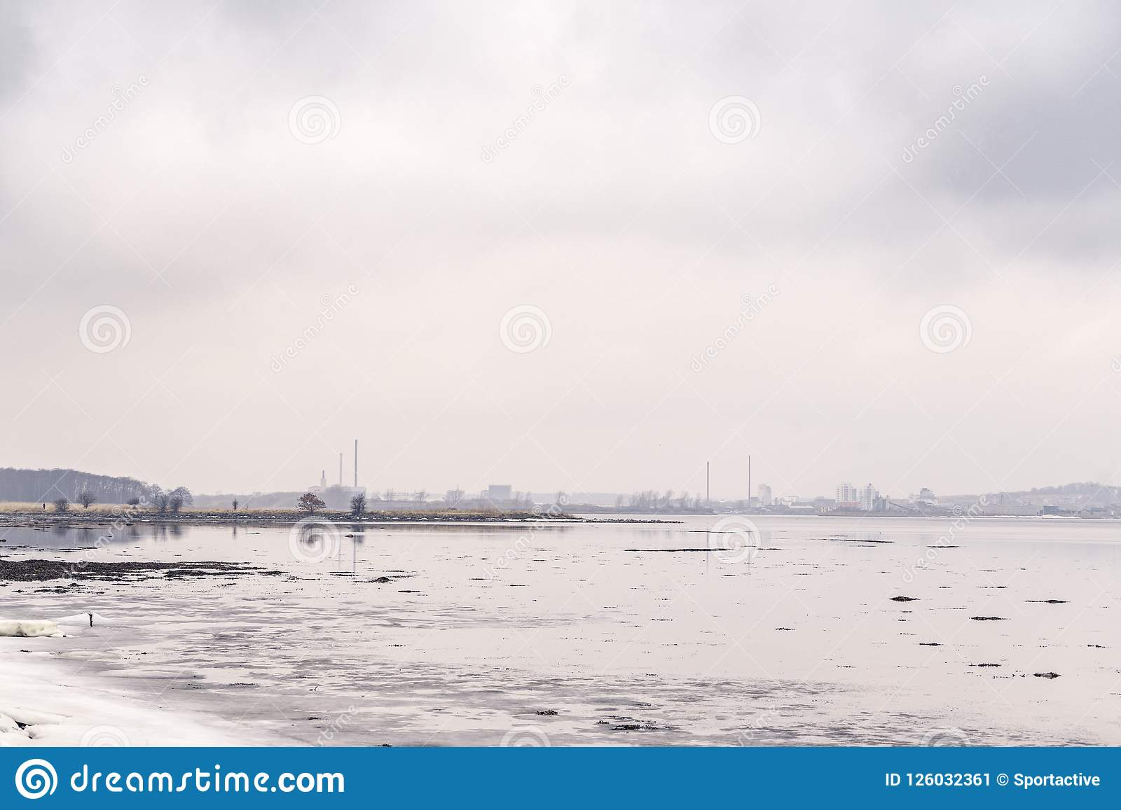 Lago congelato da una città con i fabbricati industriali