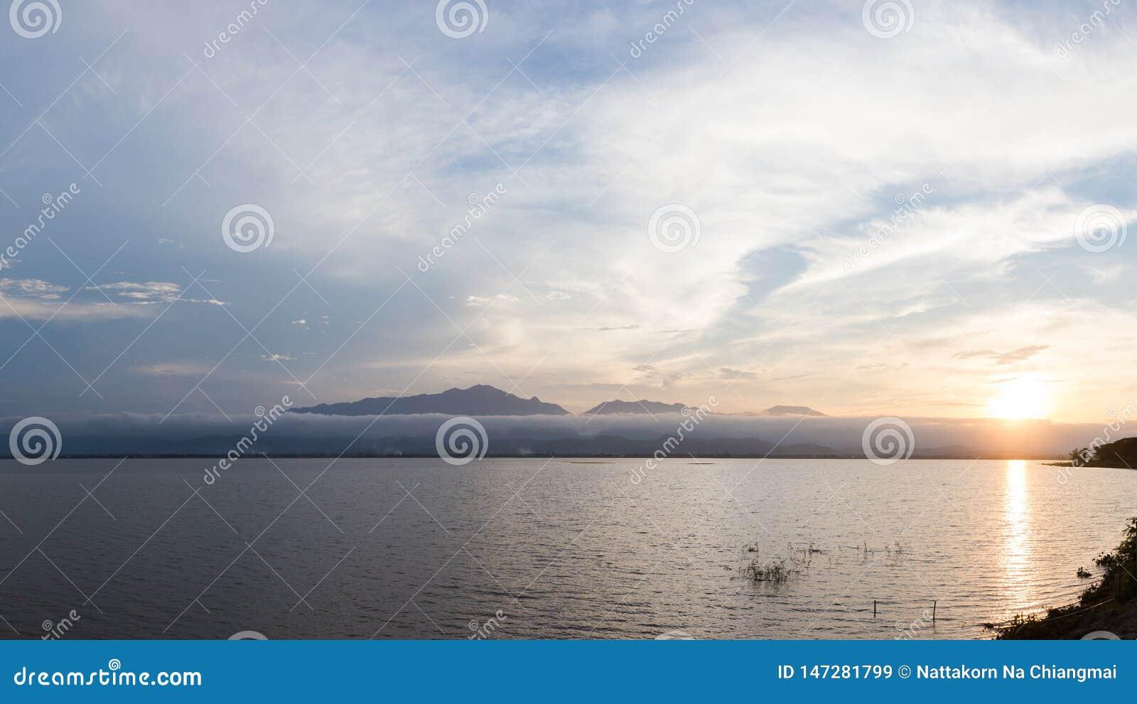 Lago e montanha bonitos durante a natureza da paisagem do por do sol no lago Phayao