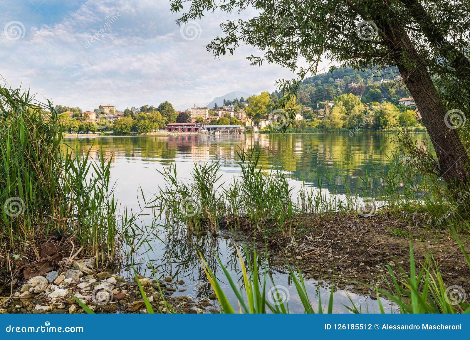 Lago hermoso en Italia septentrional Lago Varese, en el fondo la ciudad de Gavirate con su  promenade  del lago