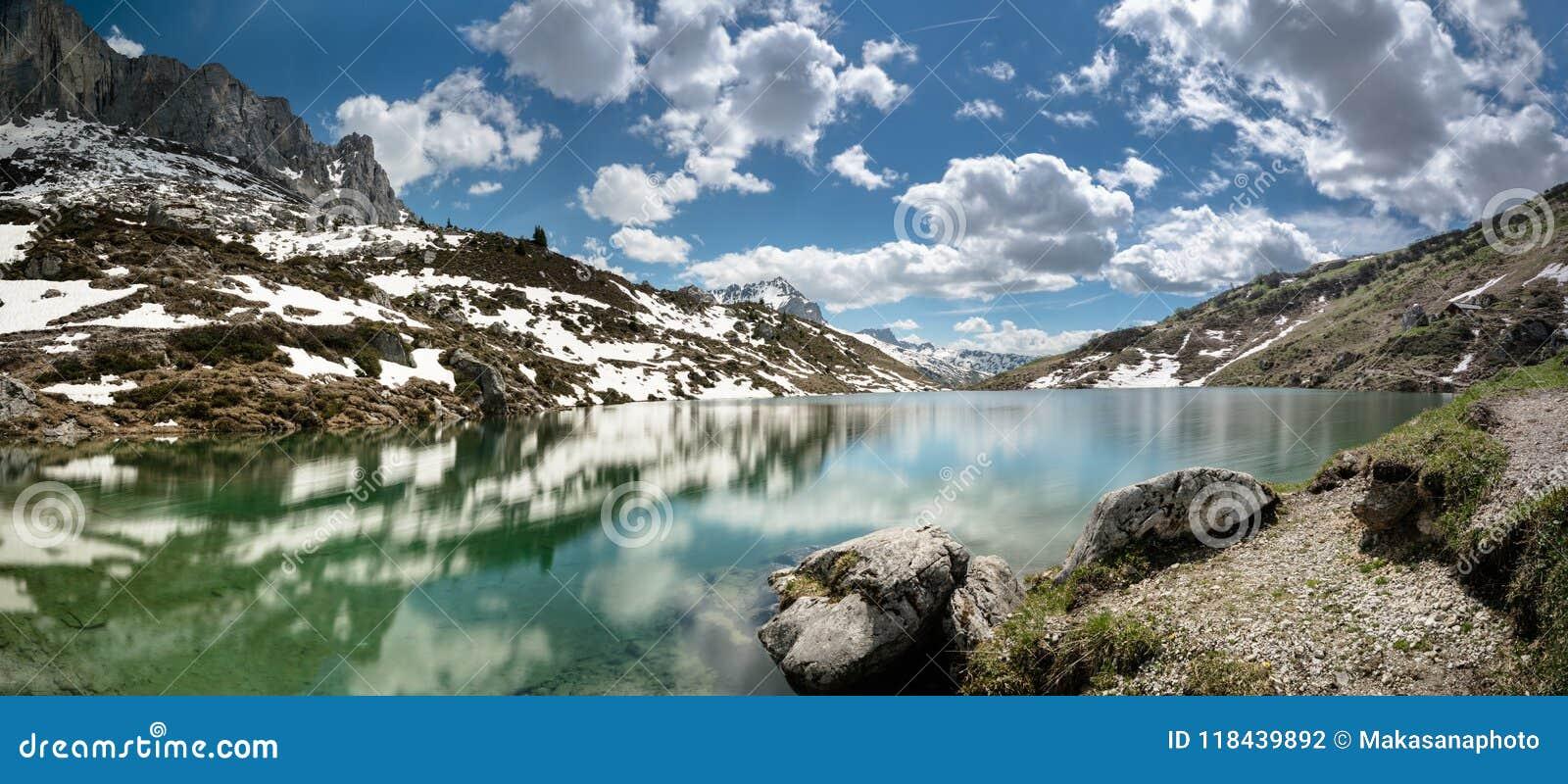 Lago lindo da montanha nos cumes com reflexões e restos da neve