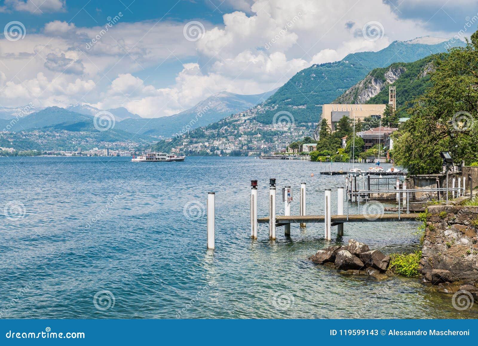 Lago Lugano Ideia do ` Italia de Campione d, famosa para seu casino visível no direito, com uma chegada do barco de turista