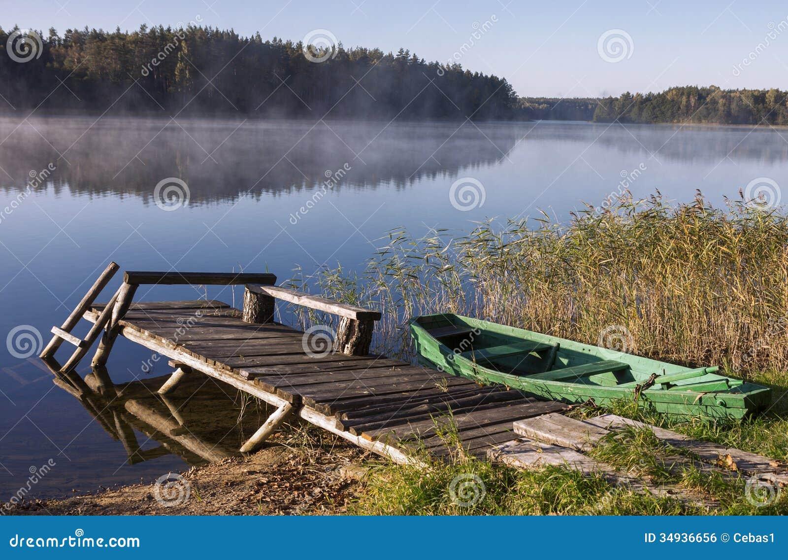 Lago nevoento com ponte e barco