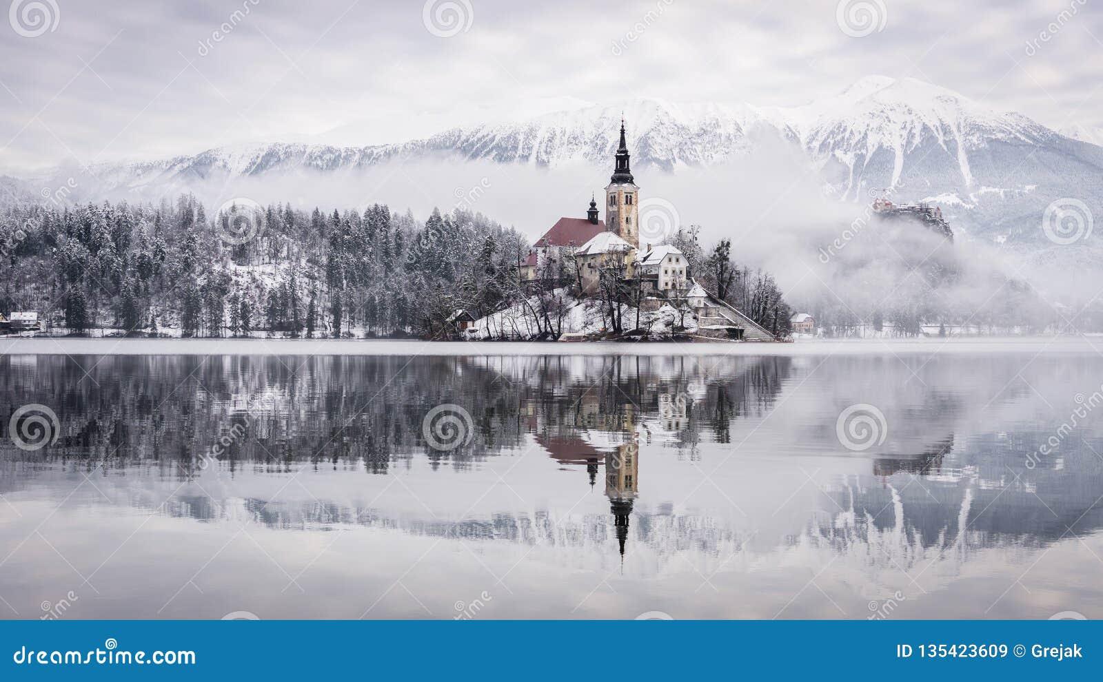 Lago sangrado con la iglesia del St Marys de la suposición en la pequeña isla - sangrada, Eslovenia, Europa