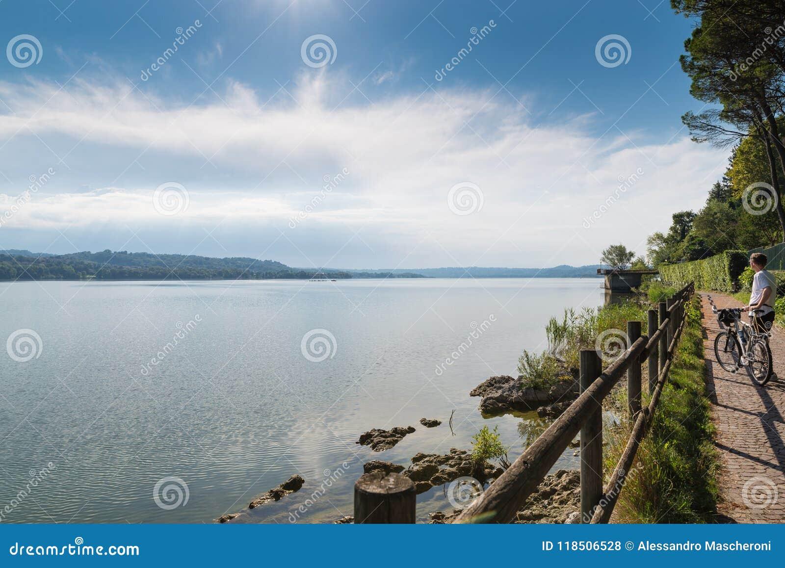 Lago Varese, paisaje del verano, Italia Lago, ciclista y ciclo - pista peatonal que corre a lo largo del lago