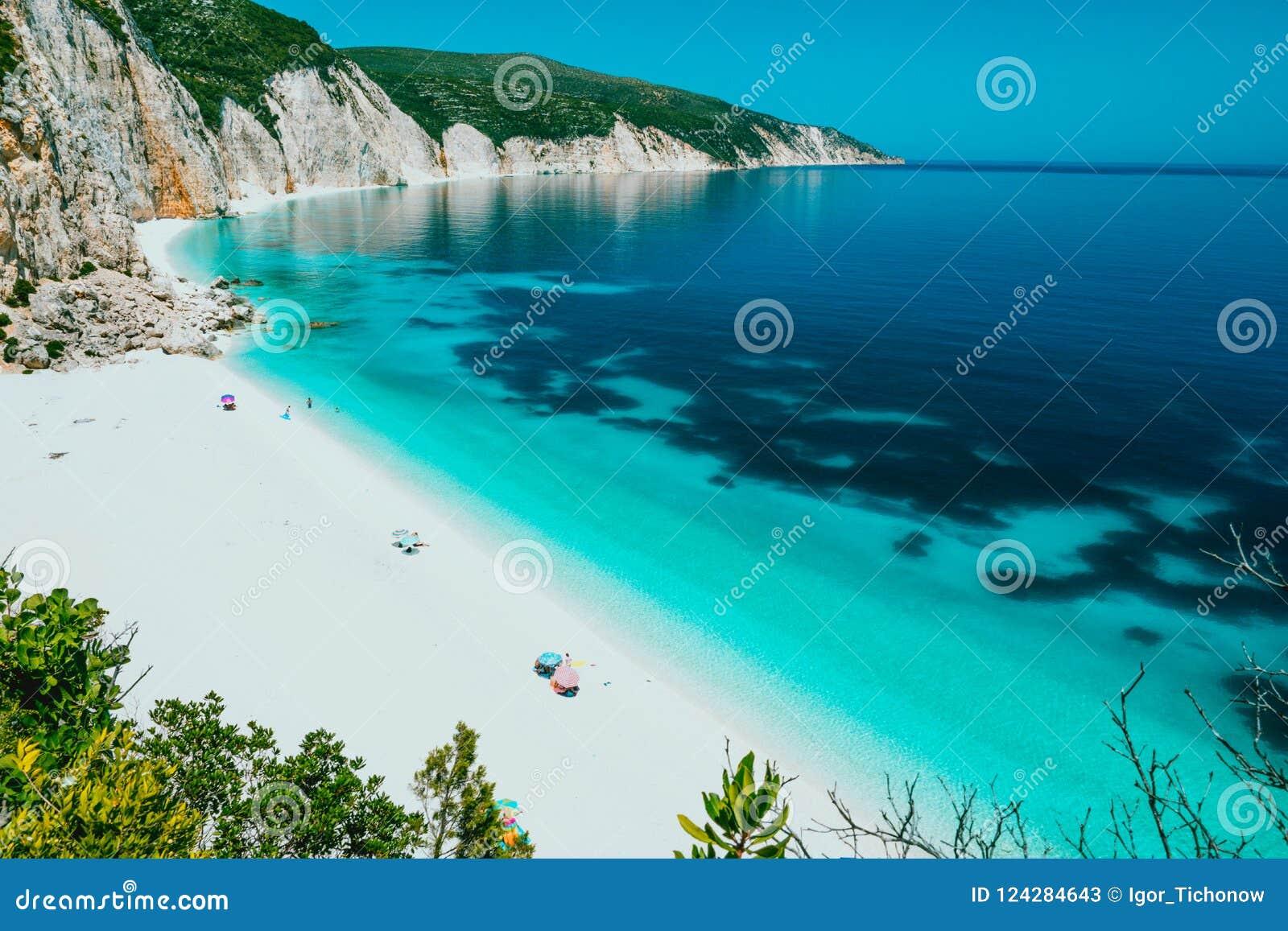 Lagoa da praia de Sunny Fteri com litoral rochoso, Kefalonia, Grécia Os turistas sob o frio do guarda-chuva relaxam perto do azul