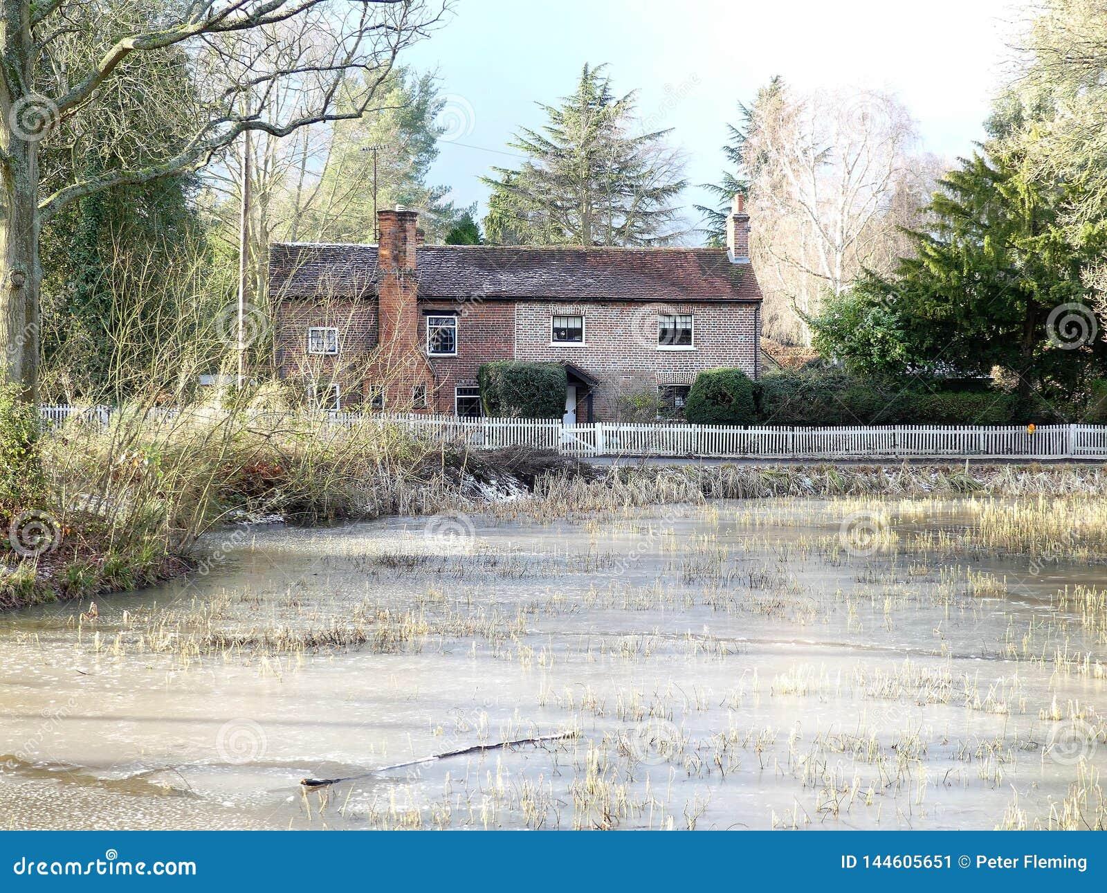 Lagoa e casas de campo comuns superiores no inverno, terra comum de Chorleywood