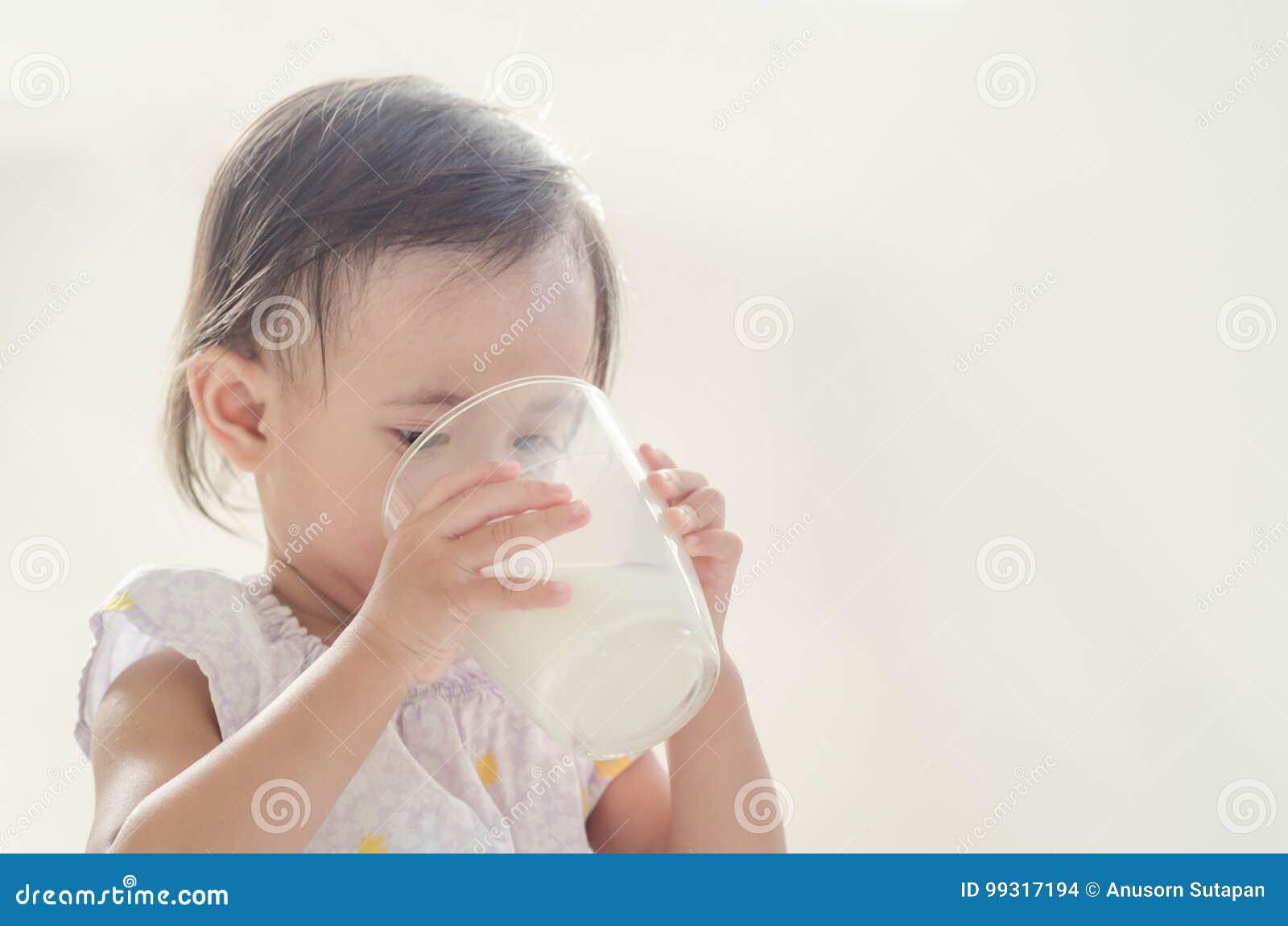 Lait boisson asiatique mignon de fille d enfant en bas âge de grand verre sur le Ba blanc
