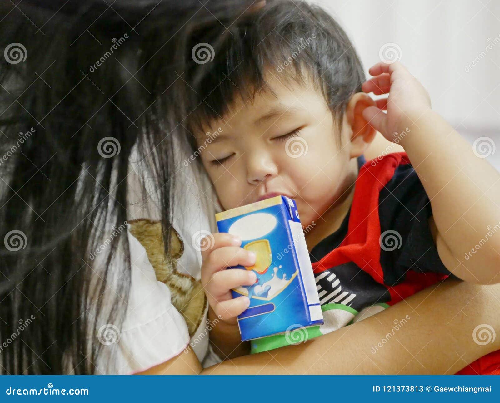 Lait boisson asiatique somnolent de bébé hors d un carton avec la paille