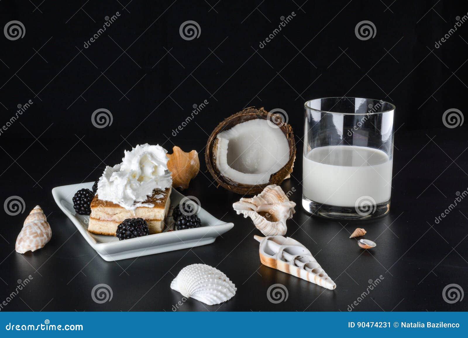 Lait et gâteau de noix de coco en verre avec des mûres