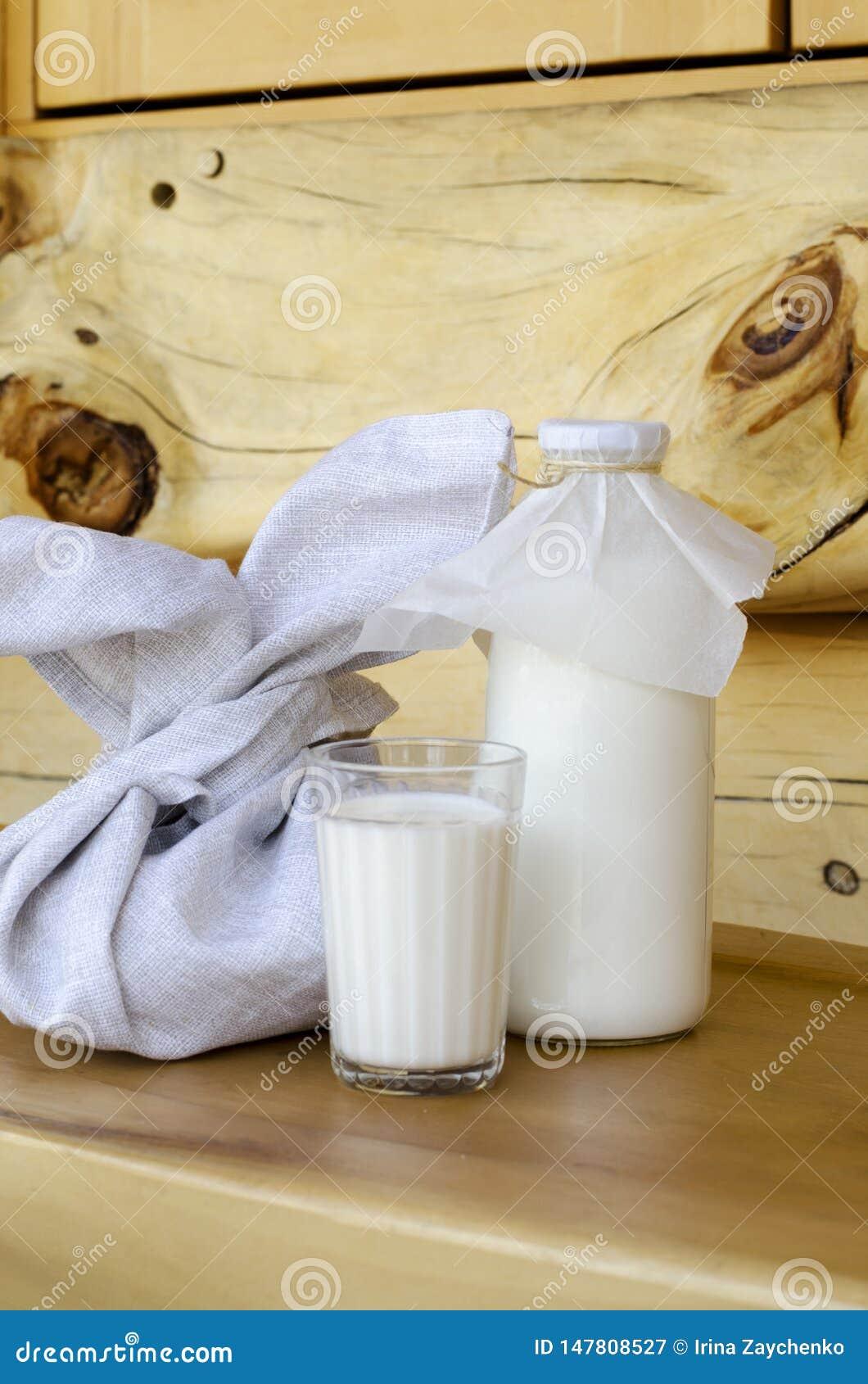 Lait frais dans une bouteille en verre et un verre, ? c?t? des tartes sur une table en bois Le concept des produits biologiques s