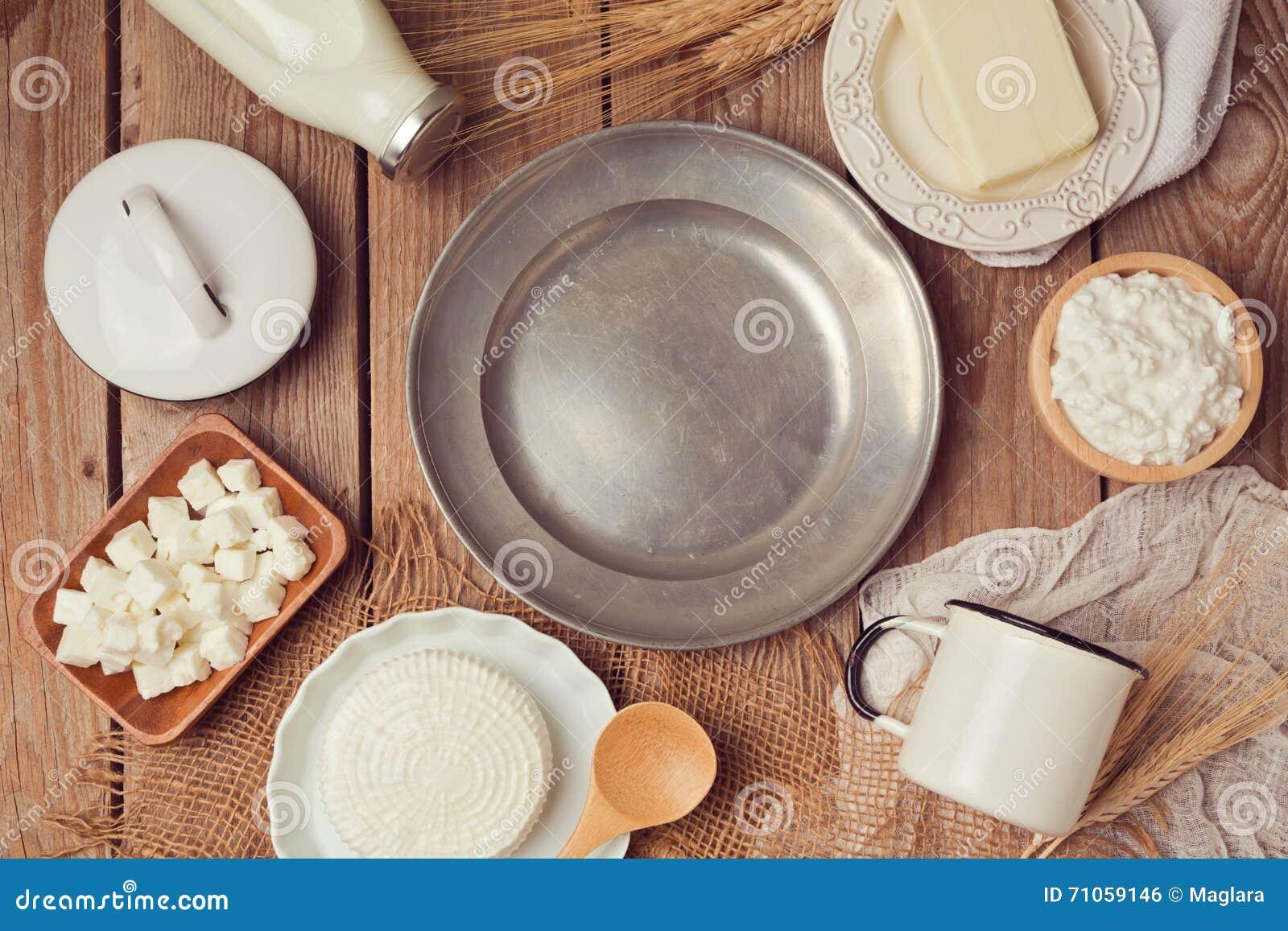lait, fromage et beurre autour de plat vide de vintage sur la table